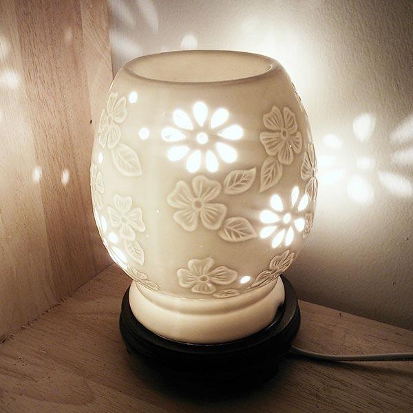 Đèn xông tinh dầu điện hoa mai họa tiết hoa đắp nổi và lủng ánh sáng xuyên qua từng lỗ tạo thêm lung linh cho căn phòng
